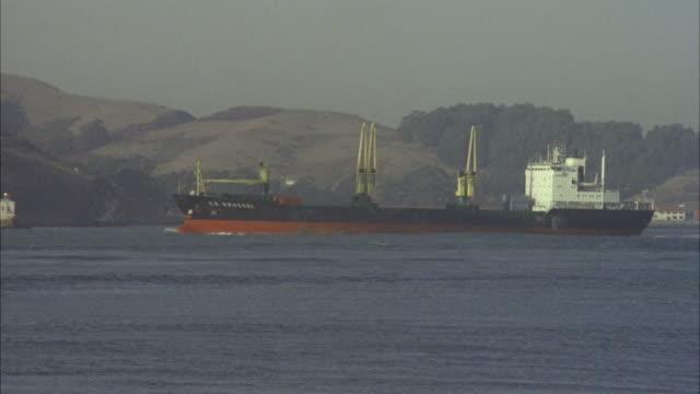 ws pan tu freighter passing under bridge of golden gate bridge / san francisco, california, united states - bay of water stock videos & royalty-free footage