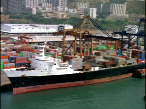 vidéos et rushes de aerial freighter with containers at dock of shipping port / hong kong - transport de marchandises par navire