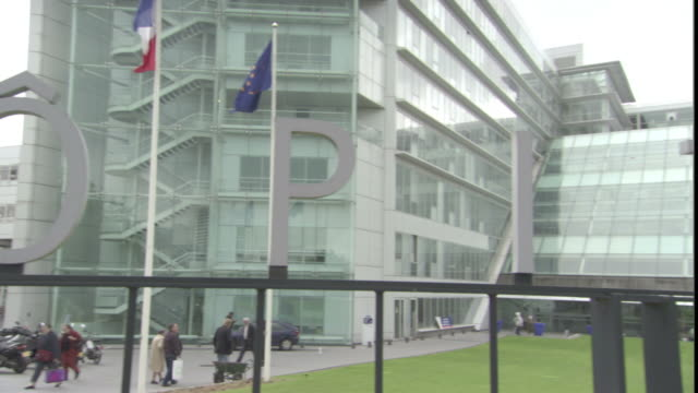 vidéos et rushes de french and european union flags wave in front of a modern hospital in paris. - hôpital