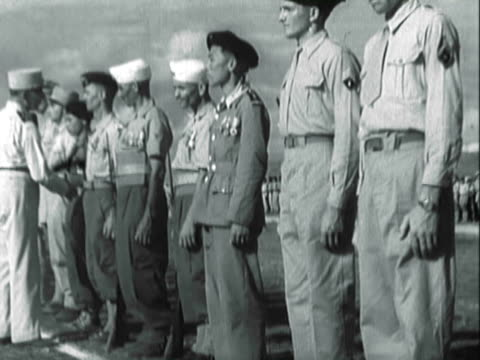 french and french colonial troops standing at attention on tarmac during award ceremony - ehre stock-videos und b-roll-filmmaterial