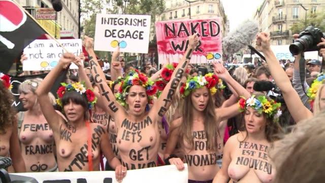 stockvideo's en b-roll-footage met french and ukrainian members of mediasavvy group femen went topless in the streets of the predominantly muslim goutte d'or neighbourhood in paris... - ontbloot bovenlichaam