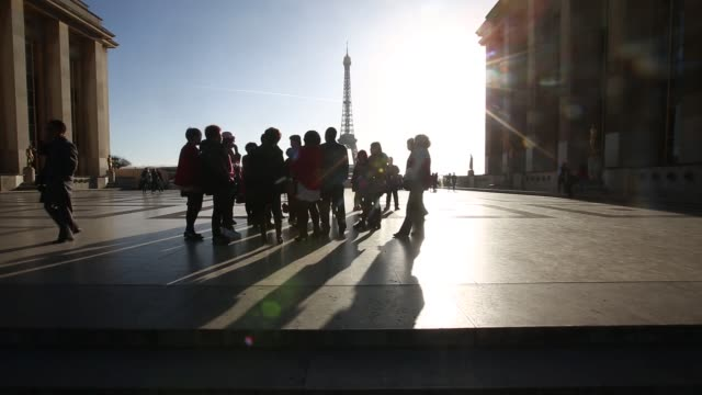 french armed police officers stand guard at the eiffel tower in paris france on sunday nov 15 tourists walk through the jardins du trocadero in front... - guarding stock videos & royalty-free footage