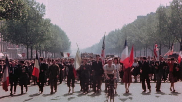 french army soldiers and officers and crowd of civilians parading through street with trucks and bicycles waving allied flags / paris france - esercito militare francese video stock e b–roll