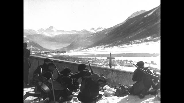 French chasseurs keep watch over an Alpine valley with a machine gun during WWI / pan long shot of mountains/ soldier sends a signal via signal lamp...