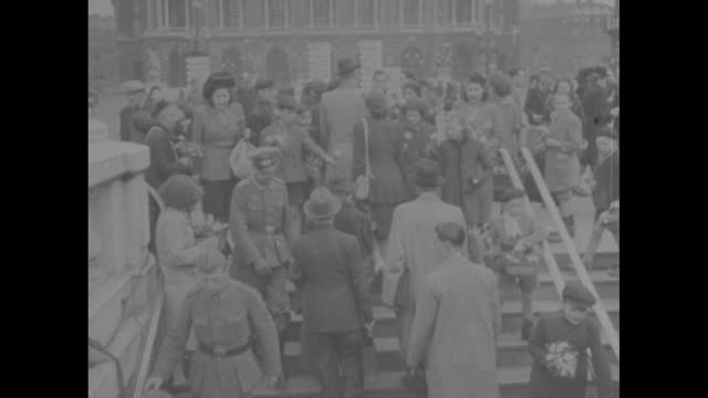 french civilians and some german soldiers descend stairs to metro station, others coming up / boy at top of stairs selling flowers to passersby /... - arc de triomphe paris stock videos & royalty-free footage