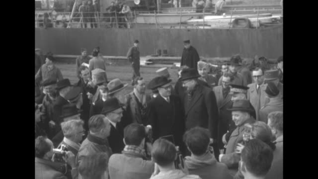 french defense minister rene pleven shakes hands with longshoremen on dock at cherbourg where us arms have arrived / good cu pleven / pleven chats... - la manche stock videos and b-roll footage