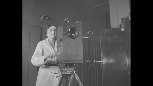 vídeos de stock e filmes b-roll de french doctor points at x-ray plate on x-ray booth as colleagues look on / woman moves to motion picture camera as doctors stand by; camera is aimed... - raio x