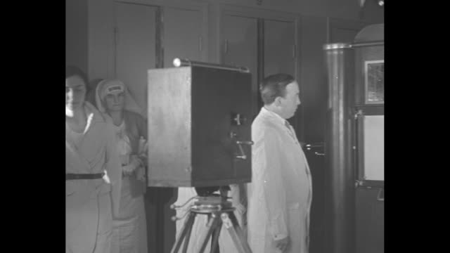french doctor points at x-ray plate on x-ray booth, speaks in french as colleagues look on at saint louis hospital in paris/ woman moves to motion... - french language stock videos & royalty-free footage