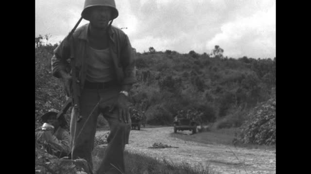 french far east expeditionary force on road through laos jungle with jeep-mounted gun in foreground, soldiers advancing away from camera in... - französische armee stock-videos und b-roll-filmmaterial