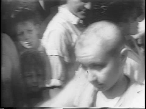 French Female Nazi sympathizer is seated in front of a crowd to get her hair cut / montage of man with scissors cutting her hair haphazardly girl...