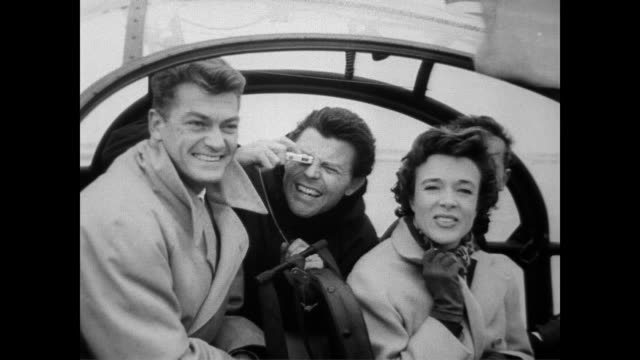stockvideo's en b-roll-footage met / french film stars gerard philipe jean marais and micheline presle smile at camera from inside new type of helicopter the alouette / helicopter fly... - 1957
