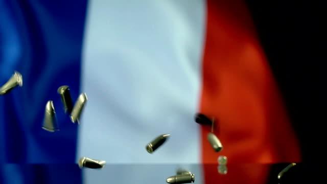 vidéos et rushes de drapeau de français derrière des balles tombant dans le mouvement lent - crime organisé