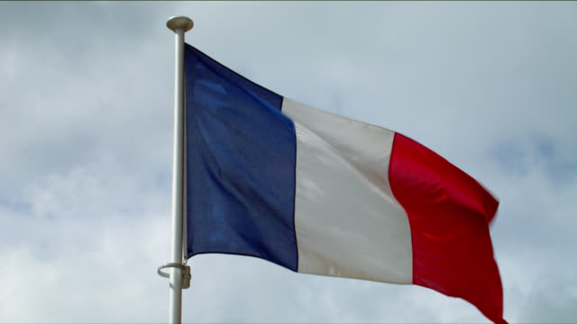French flag blows in cloudy sky