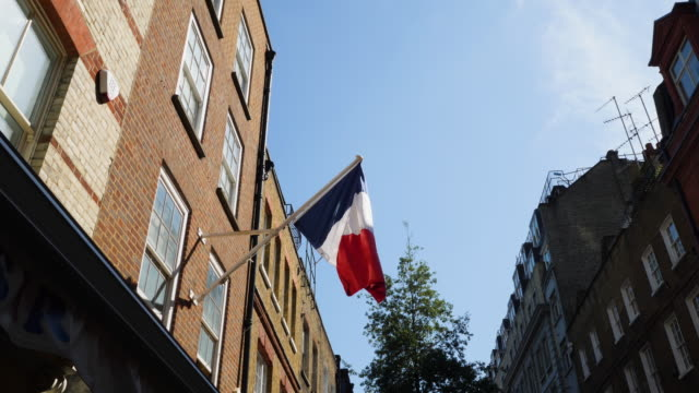 A French flag blows in the breeze in a London street