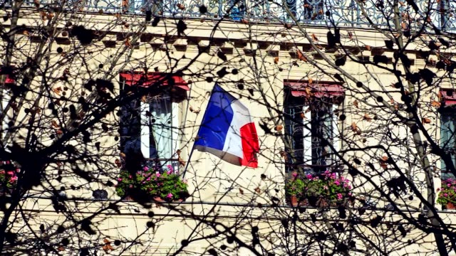French flag hanging from a window waving outside a building from Paris France