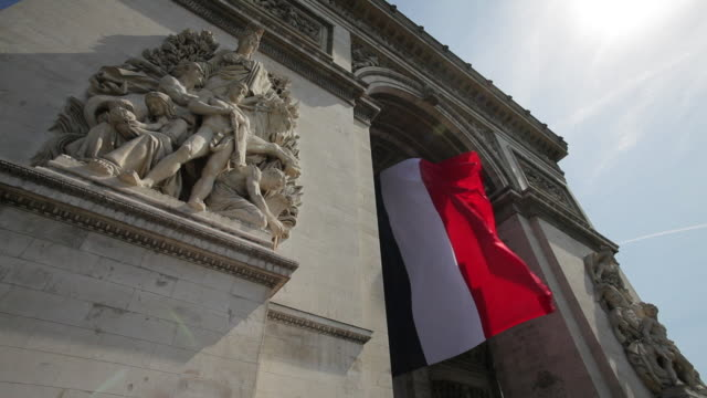 a french flag hangs from the arc de triomphe in paris, france. - french flag stock videos & royalty-free footage