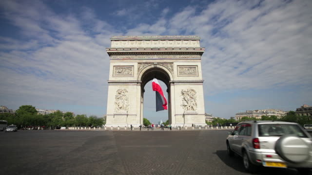 a french flag hangs from the arc de triomphe in paris, france. - 凱旋門点の映像素材/bロール