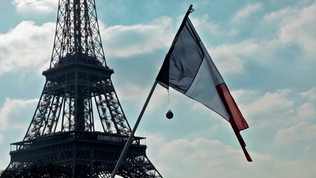 French flag in front of Eiffel Tower