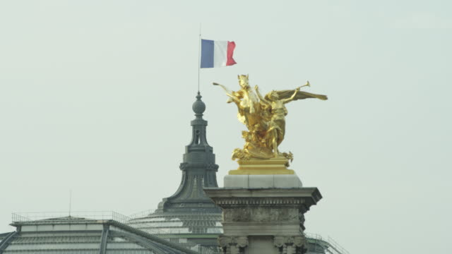 LS  French flag, the tricolor, flying over the Grand Palais with gilded statue on Alexandre III bridge in foreground