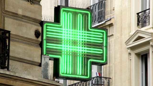 french flashing pharmacy sign in paris with flag behind - pharmacy stock videos and b-roll footage