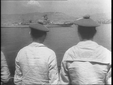 French fleet in harbor in Toulon French sailors look out water / sailors climb up ladder / ship passing French submarine flying flag / French...