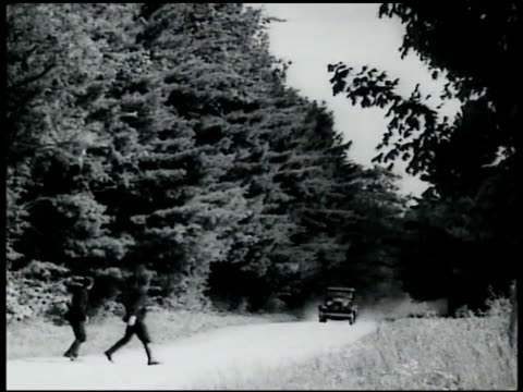 vidéos et rushes de french gendarmes attempting to wave car to stop two gendarmes on country road waving speeding car to stoptwo gendarmes talking to stopped driver - 1935