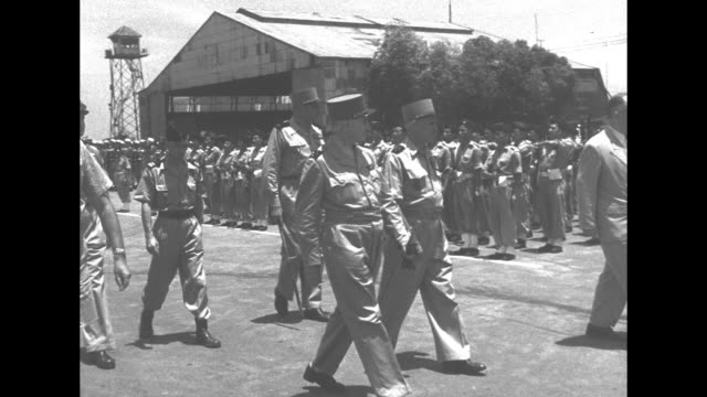 French General Henri Navarre deplanes in Laos and shakes hands with military officials in receiving line/ Navarre inspects troops of French Far East...
