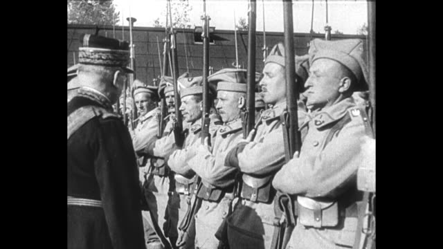 french general louis archinard walks past polish troops standing at attention / archinard decorates two soldiers taps each shoulder with stick kisses... - polen stock-videos und b-roll-filmmaterial
