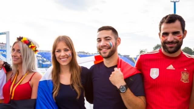 CU french, german, italian and spanish sport fans celebrating at soccer stadium