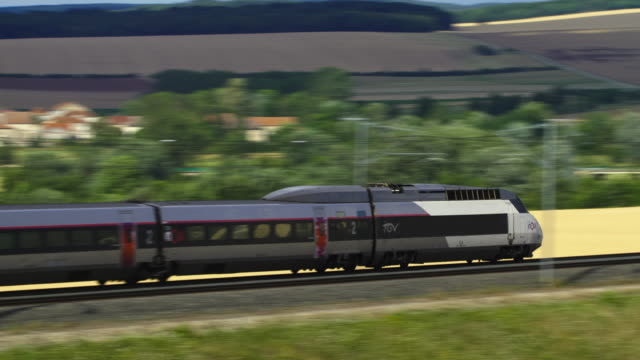 vidéos et rushes de french high speed tgv train approached bridge past rolling landscape of wheat fields, meuse department, lorraine - train de banlieue