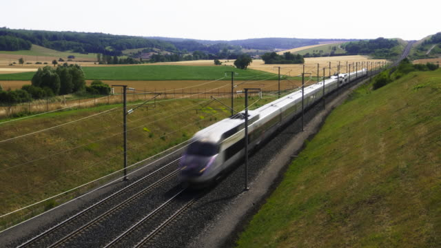 french high speed tgv train approached on long railroad tracks in rolling countryside, meuse department, lorraine - tgv点の映像素材/bロール