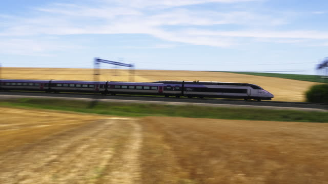vidéos et rushes de french high speed tgv train approaches from mound past wheat field and round straw bales, meuse department, lorraine - train