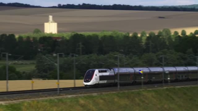 french high speed tgv train tgv travels over bridge past wheat fields, meuse department, lorraine - tgv点の映像素材/bロール