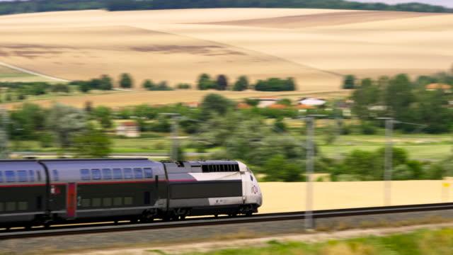 french high speed tgv train travels over bridge past wheat field, marne department, champagne, france - tgv点の映像素材/bロール