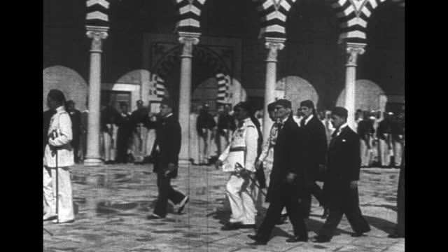 [french language vo throughout ] formally dressed and uniformed men cross courtyard at court of dar soulaimania in tunis with striped archways and... - tassel stock videos & royalty-free footage