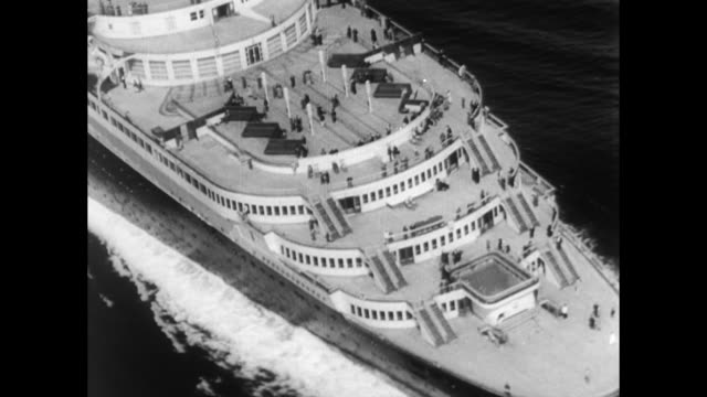 French luxury ocean liner arrives in New York at the end of its maiden voyage / aerial view of top deck as it floats past camera / surrounded by...