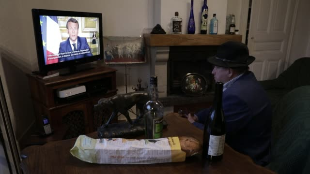stockvideo's en b-roll-footage met french man in watching on television the speech of the french president emmanuel macron concerning the covid19 health crisis during lockdown on april... - aankondigingsbericht