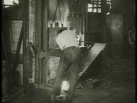 french men working in cannon factory cu cannon barrel turning in machine vs worker w/ clamp handling hot iron putting it through machine workers w/... - artiglieria video stock e b–roll
