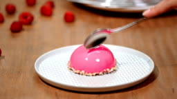 French mousse cake covered with raspberry glaze. Pink modern European dessert.