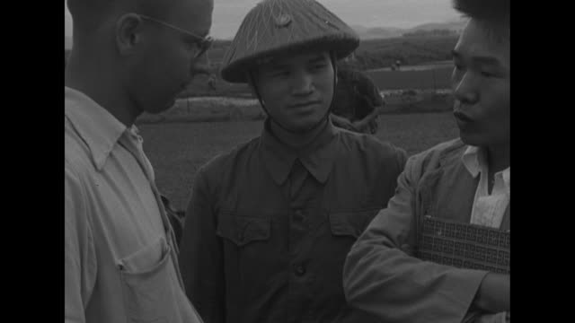 french mp at entrance to facility at which truce talks will be held / vietnamese guard / two journalists chat as viet minh guard looks on / viet minh... - vangen stock-videos und b-roll-filmmaterial