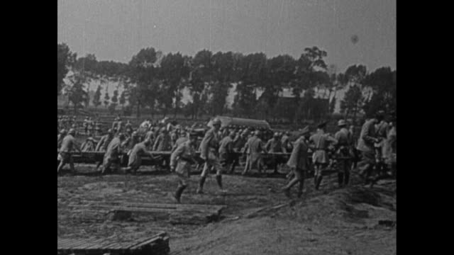 french officers working on flotation devices / french soldiers carrying bridges to river and pushing them across river / soldiers running across... - pontoon bridge stock videos and b-roll footage
