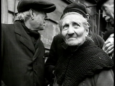 stockvideo's en b-roll-footage met french people on line, 'cuisine central' building. elderly couple waiting. soup being scooped into pot for elderly lady, elderly man next on line.... - 1946