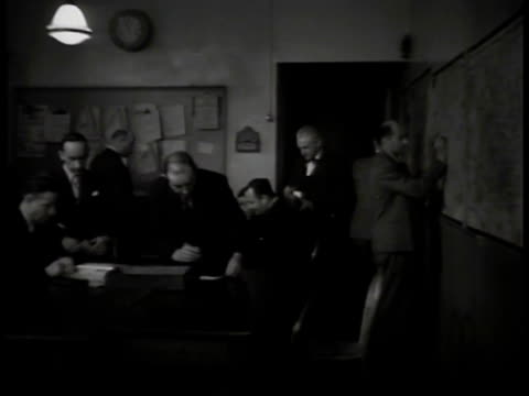 vidéos et rushes de french plain-clothes policemen in room, one making notes on paper, two escorting man into room, male finger printing male. - seconde guerre mondiale