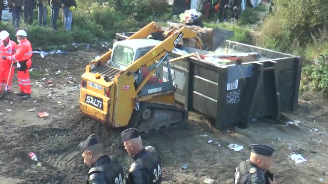 vídeos de stock e filmes b-roll de french police stand guard at the notorious 'jungle' camp as authorities begin to demolish the site on october 25 2016 in calais france many migrants... - crise de migrantes europeia 2015 2016