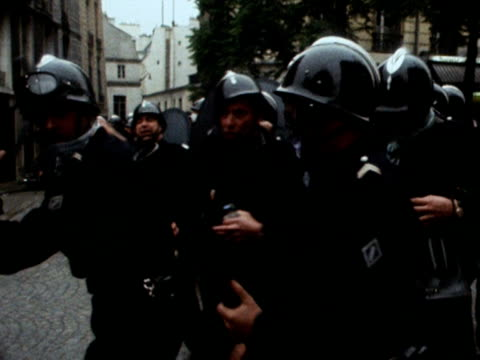 stockvideo's en b-roll-footage met a french policeman fires a concussion grenade at student protestors during the parisian riots 1968 - 1968