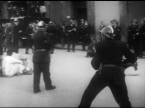 vídeos de stock, filmes e b-roll de french policeman w/ nightstick chasing young male police bg men sitting in group w/ policeman beside martial law vs open top trucks of seated... - civil