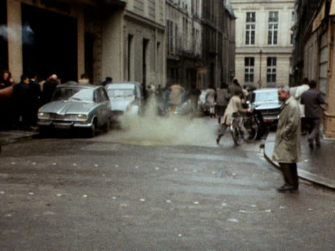 french policemen throw concussion grenades to disperse crowds during the paris student riots 1968 - 1968 stock-videos und b-roll-filmmaterial