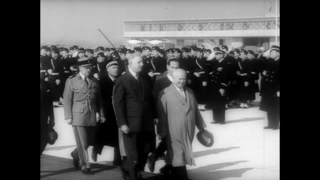 French President Charles de Gaulle arrives with other officials to greet Khruschev at the airport / motorcade drives through the city as spectators...