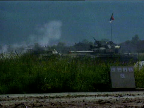 French President Francois Mitterrand helped out of armored personnel carrier / Serbian tank on runway at Sarajevo airport sniper running Serbian...