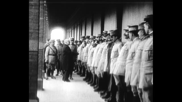 french president raymond poincare and exprime minister aristide briand walk along sidewalk / poincare shakes hands with a line of officers / poincare... - esercito militare francese video stock e b–roll